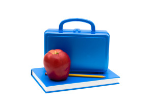 Blue lunch box and apple on a blue book isolated on white, School Lunches